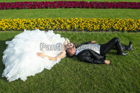 newlyweds posing on lawn
