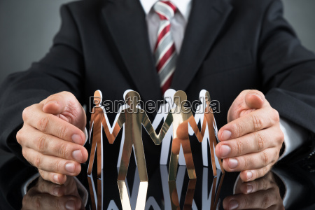 businessperson protecting cutout figures