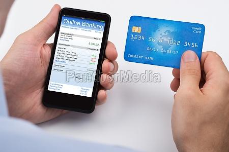 person mit kreditkarte und handy