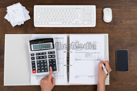 person calculating invoice with calculator