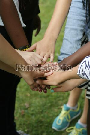 multikulturelles team haelt haende zusammen
