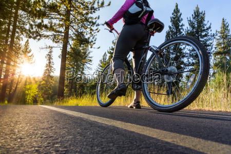 biker bei sonnenuntergang auf asphaltweg