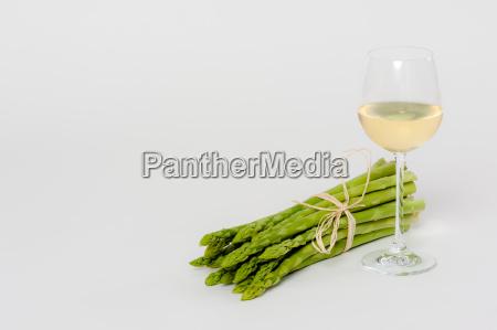 gruener spargel liegend mit einem glas