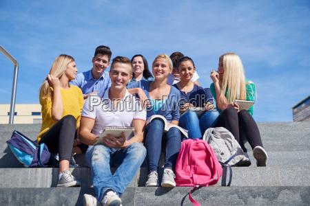 studenten sitzen draussen auf den stufen