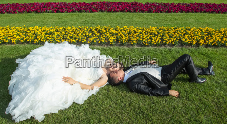 bride and groom lying on lawn