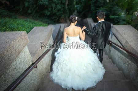 newlyweds walking down stone stairs