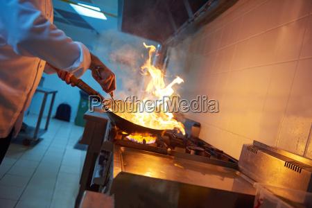 kuechenchef in der hotelkueche bereitet speisen