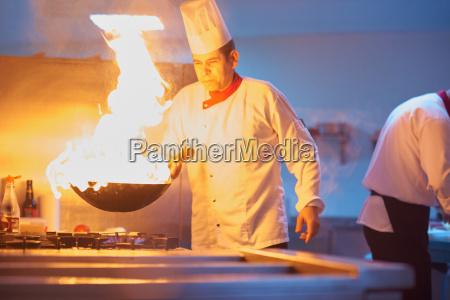 chef in der hotelkueche bereiten essen