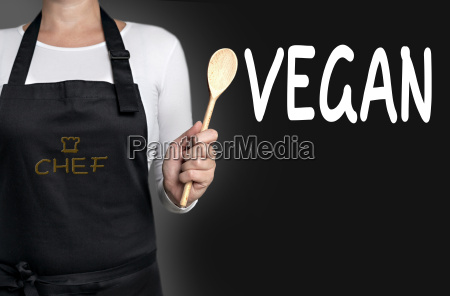 vegan koch haelt kochloeffel hintergrund
