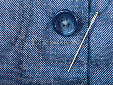 befestigung des knopfes an blauem seidengewebe