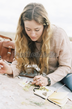 woman sitting on a rock putting