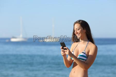 sunbather maedchen mit einem smartphone auf
