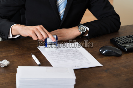 businessman stamping contract paper