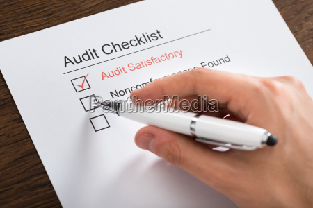 person filling audit checklist form at