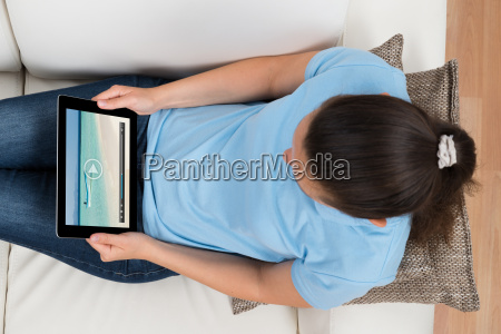 woman watching video on digital tablet
