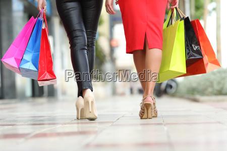 zwei modefrauen beine gehen mit einkaufstaschen
