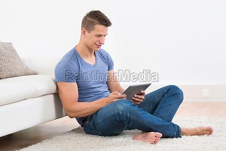 man with digital tablet sitting near