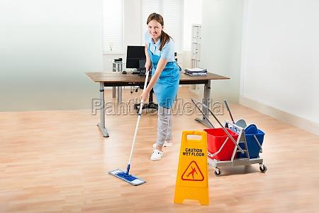 female janitor cleaning hardwood floor in
