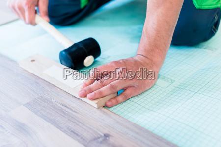 heimwerker beim bodenlegen auf renovierung