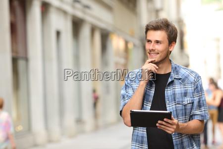 mann mit einem tablet denken in