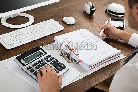 geschaeftsmann ueberpruefung rechnung mit calculator