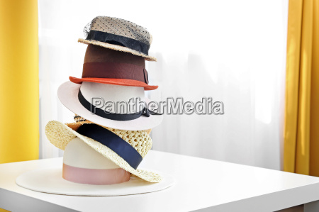 hat stack on white table in