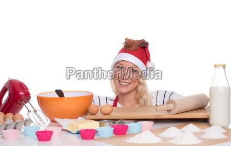 frau mit weihnachtsmuetze backt muffins