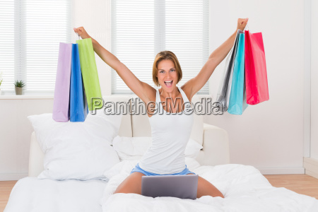 excited woman holding shopping bags