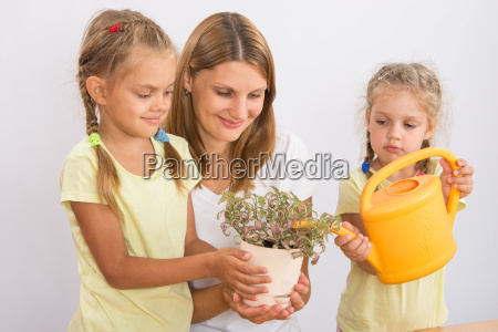 mother and daughter watering houseplants