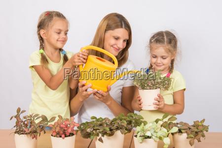joyful mother and children watering flowers