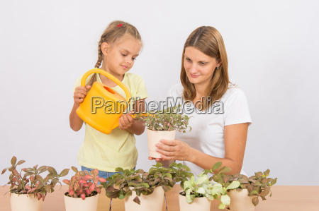 mom and daughter watering potted plants