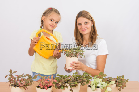mom and daughter watering houseplants