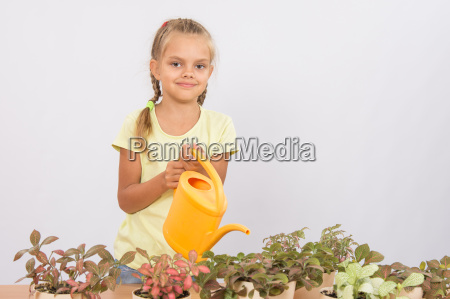 six year girl watering potted plants