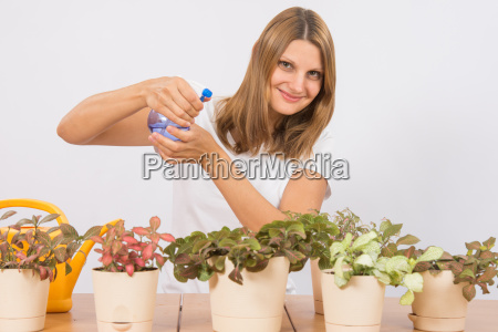 she sprinkles potted plants from a