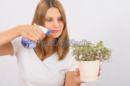 girl watering a flower from the