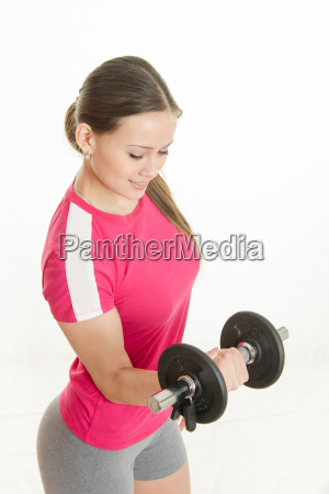 sportswoman looking at dumbbell in the