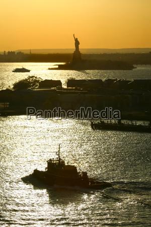 boats sailing next to libery statue