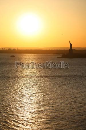 liberty statue and sunset