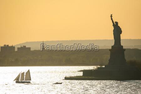 sailboat next to liberty statue