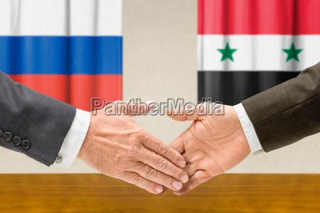 vertreter russlands und syriens reichen sich