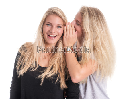 two blond young girls whisper together
