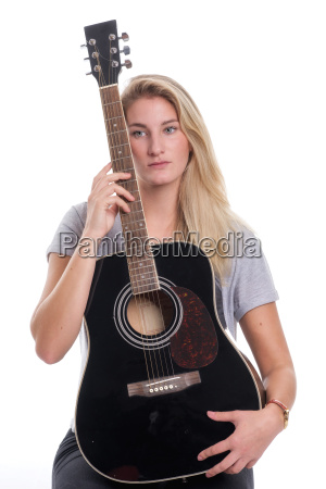 young blond girl holds a guitar