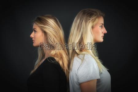 2 blonde frauen stehen ruecken an