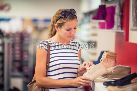 beautiful young woman shopping for shoes