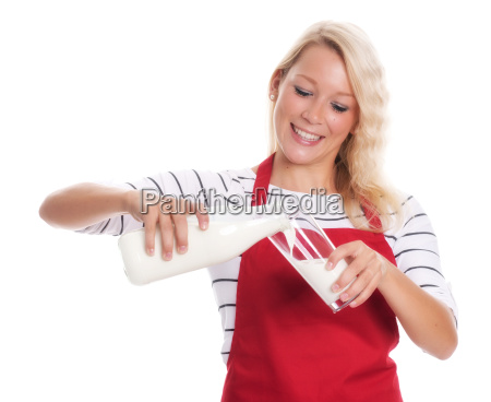 housewife in apron pouring milk into