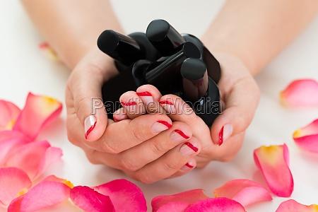 woman hands holding nail varnish bottles