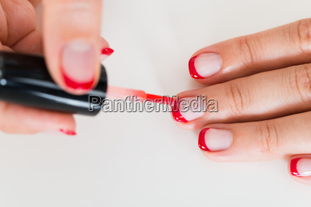 female hands applying nail varnish