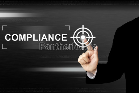 business hand pushing compliance button on