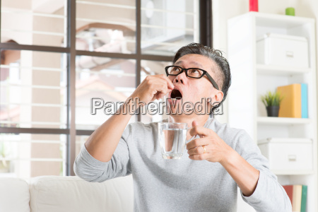 mature 50s asian man eating medicine