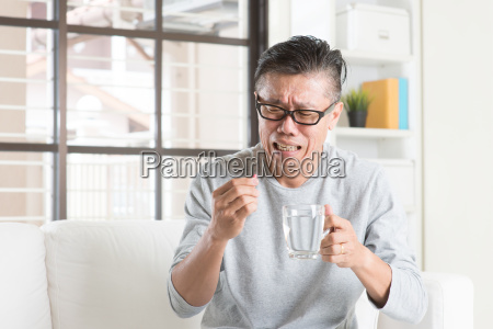 mature asian chinese man eating medicine